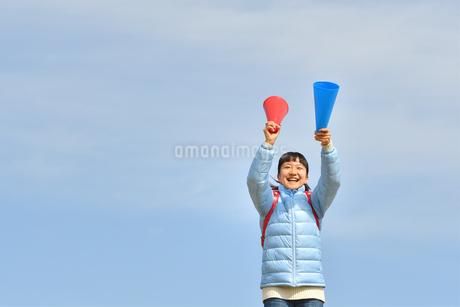 青空で応援する女の子(冬)の写真素材 [FYI02980902]