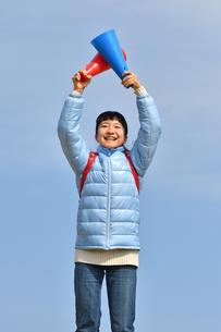 青空で応援する女の子(冬)の写真素材 [FYI02980904]