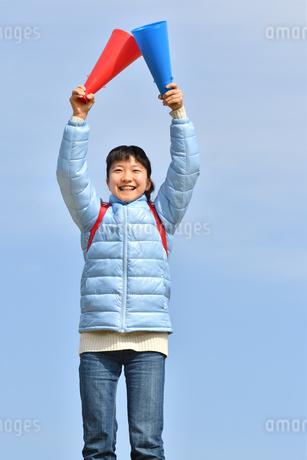 青空で応援する女の子(冬)の写真素材 [FYI02980906]