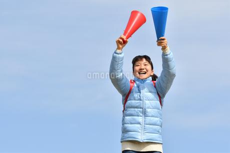 青空で応援する女の子(冬)の写真素材 [FYI02980909]