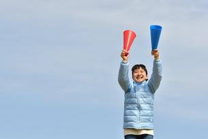 青空で応援する女の子(冬)の写真素材 [FYI02980911]