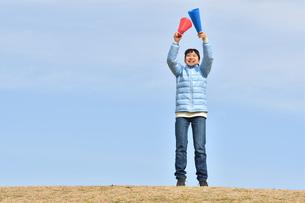 青空で応援する女の子(冬)の写真素材 [FYI02980916]