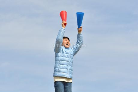 青空で応援する女の子(冬)の写真素材 [FYI02980918]