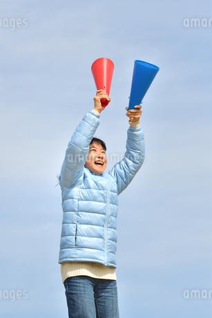 青空で応援する女の子(冬)の写真素材 [FYI02980920]
