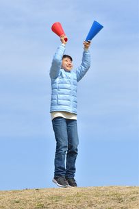 青空で応援する女の子(冬)の写真素材 [FYI02980922]