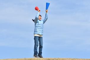 青空で応援する女の子(冬)の写真素材 [FYI02980925]