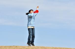 青空で応援する女の子(冬)の写真素材 [FYI02980926]