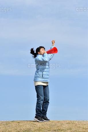 青空で応援する女の子(冬)の写真素材 [FYI02980927]