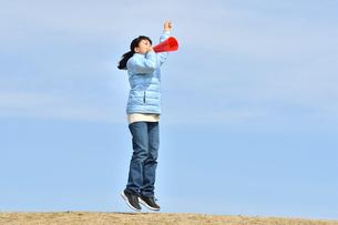 青空で応援する女の子(冬)の写真素材 [FYI02980929]