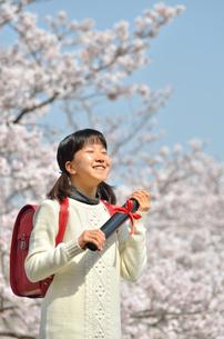 青空で卒業証書を持って笑う小学生の女の子(桜、ランドセル)の写真素材 [FYI02981227]
