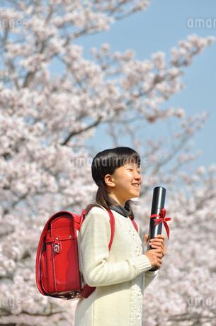 青空で卒業証書を持って笑う小学生の女の子(桜、ランドセル)の写真素材 [FYI02981228]