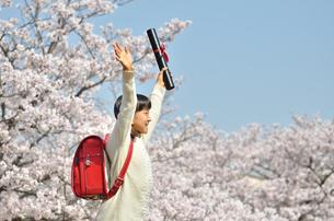 青空で卒業証書を持って笑う小学生の女の子(桜、ランドセル)の写真素材 [FYI02981229]
