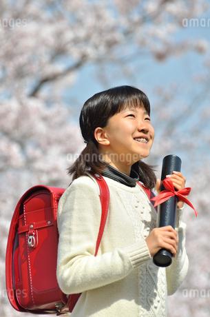 青空で卒業証書を持って笑う小学生の女の子(桜、ランドセル)の写真素材 [FYI02981231]