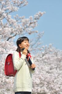青空で卒業証書を持って笑う小学生の女の子(桜、ランドセル)の写真素材 [FYI02981233]