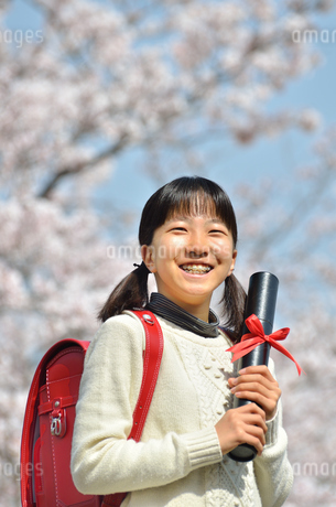 青空で卒業証書を持って笑う小学生の女の子(桜、ランドセル)の写真素材 [FYI02981234]