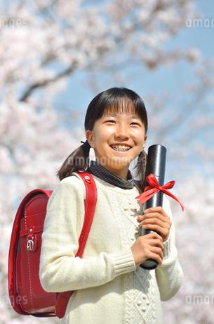 青空で卒業証書を持って笑う小学生の女の子(桜、ランドセル)の写真素材 [FYI02981235]