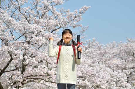 青空で卒業証書を持って笑う小学生の女の子(桜、ランドセル)の写真素材 [FYI02981236]