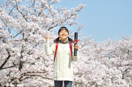青空で卒業証書を持って笑う小学生の女の子(桜、ランドセル)の写真素材 [FYI02981237]