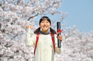 青空で卒業証書を持って笑う小学生の女の子(桜、ランドセル)の写真素材 [FYI02981238]