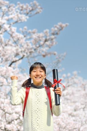 青空で卒業証書を持って笑う小学生の女の子(桜、ランドセル)の写真素材 [FYI02981239]