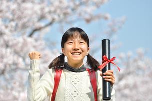 青空で卒業証書を持って笑う小学生の女の子(桜、ランドセル)の写真素材 [FYI02981240]