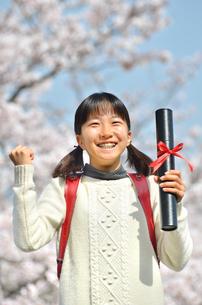 青空で卒業証書を持って笑う小学生の女の子(桜、ランドセル)の写真素材 [FYI02981241]