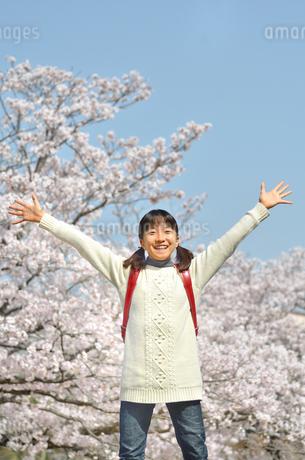 青空で笑う小学生の女の子(桜、ランドセル)の写真素材 [FYI02981244]