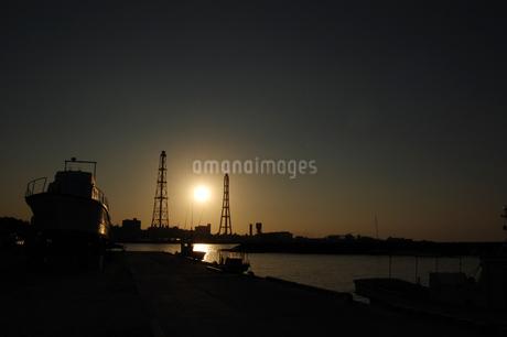 夕日でシルエットになる火力発電用の鉄塔のある港の写真素材 [FYI02981837]