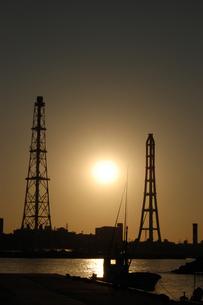 夕日でシルエットになる火力発電用の鉄塔のある港の写真素材 [FYI02981838]