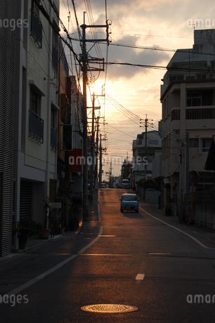 沖縄の町中の道を照らす夕焼けの写真素材 [FYI02981843]
