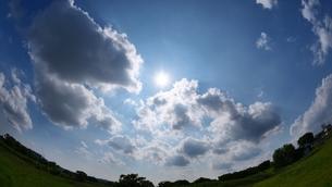 太陽が眩しく広がる雲の多い空の写真素材 [FYI02982747]