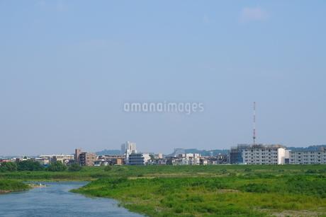 青空の下の川の対岸に広がる街の写真素材 [FYI02982755]