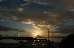 朝日にも夕日にも見える空とシルエットの港の写真素材 [FYI02982935]