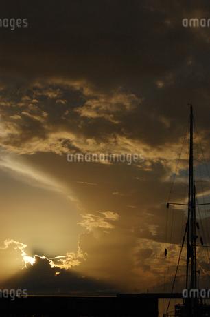 朝日にも夕日にも見える空とシルエットの港の写真素材 [FYI02982936]