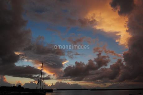 朝日にも夕日にも見える空とシルエットの港の写真素材 [FYI02982937]