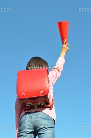 青空で応援する小学生の女の子(後姿、ランドセル)の写真素材 [FYI02983161]