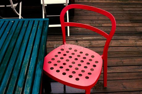 雨上がりのテラスに置かれたスチール製の赤い椅子の写真素材 [FYI02983999]
