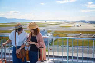 飛行場で撮った写真を見ながら談笑する二人の女性の写真素材 [FYI02985972]