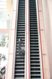 エスカレーターに乗るサラリーマンの写真素材 [FYI02985979]