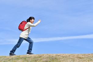 青空で走る小学生の女の子(ランドセル、芝生広場)の写真素材 [FYI02986258]