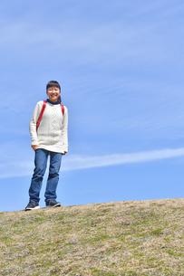 青空で笑う小学生の女の子(ランドセル、芝生広場)の写真素材 [FYI02986259]