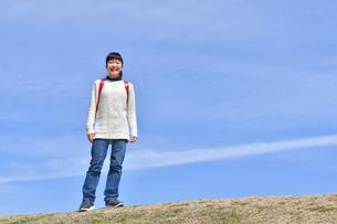 青空で笑う小学生の女の子(ランドセル、芝生広場)の写真素材 [FYI02986260]