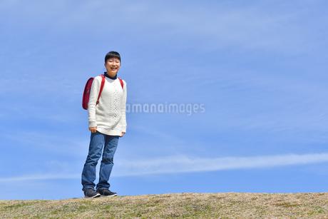青空で笑う小学生の女の子(ランドセル、芝生広場)の写真素材 [FYI02986261]