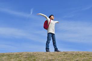青空で両手を広げる小学生の女の子(ランドセル、芝生広場)の写真素材 [FYI02986266]