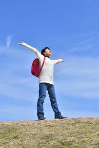 青空で両手を広げる小学生の女の子(ランドセル、芝生広場)の写真素材 [FYI02986267]