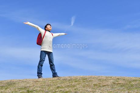 青空で両手を広げる小学生の女の子(ランドセル、芝生広場)の写真素材 [FYI02986268]