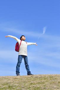 青空で両手を広げる小学生の女の子(ランドセル、芝生広場)の写真素材 [FYI02986269]