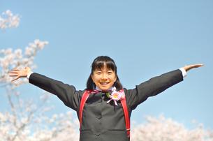 小学校を卒業する女の子(桜、青空、ランドセル)の写真素材 [FYI02986513]