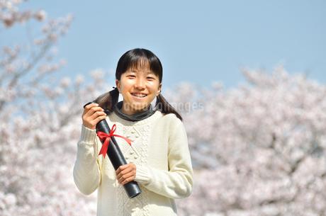 小学校を卒業する女の子(桜、青空)の写真素材 [FYI02986764]