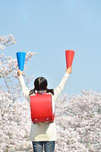 青空で応援する小学生の女の子(メガホン、後姿)の写真素材 [FYI02986782]